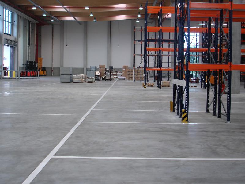 Betonboden in einer Lagerhalle mit Regalen für Paletten